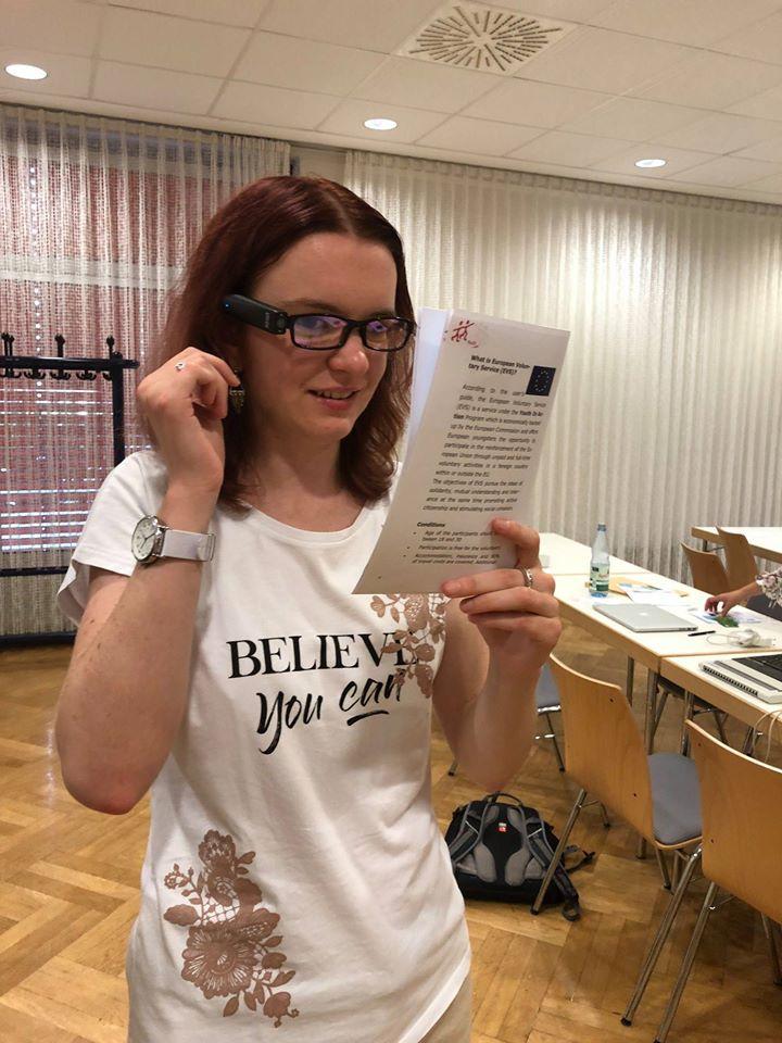 žena s kamerou OrCam připevněnou ke brýlím