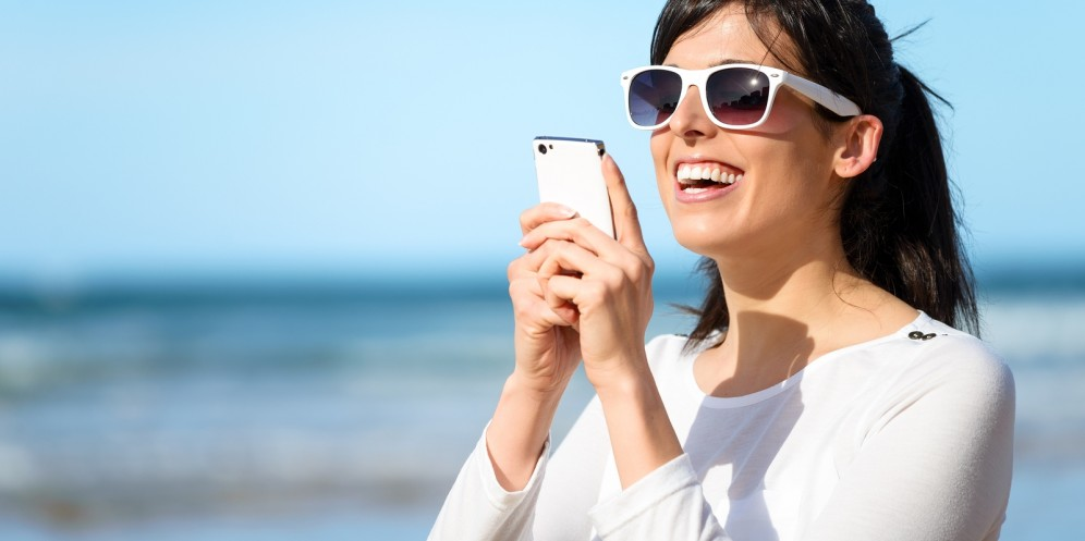 A woman wearing sunglasses and working on her smartphone