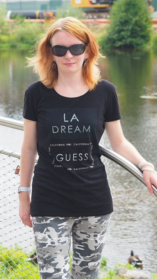 The author of the blog. She is standing outside during summer, wearing sunglasses and black T-shirt. It is sunny. There is nature and river in the background