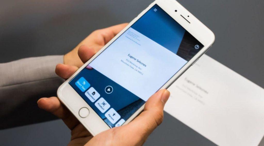 Pohled na ruku, která drží iPhone se spuštěnou aplikací Seeing AI