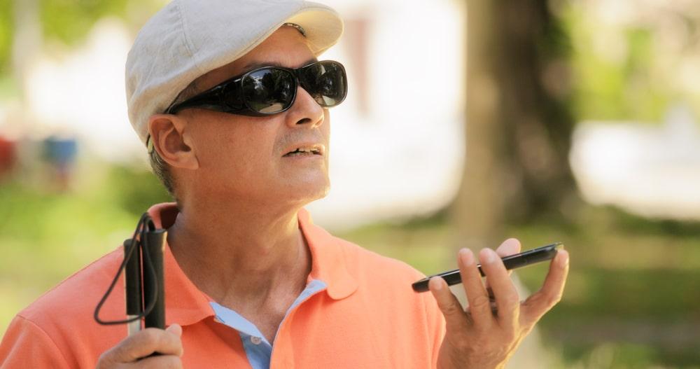 Nevidomý muž drží v ruce telefon a pomocí gest jej ovládá
