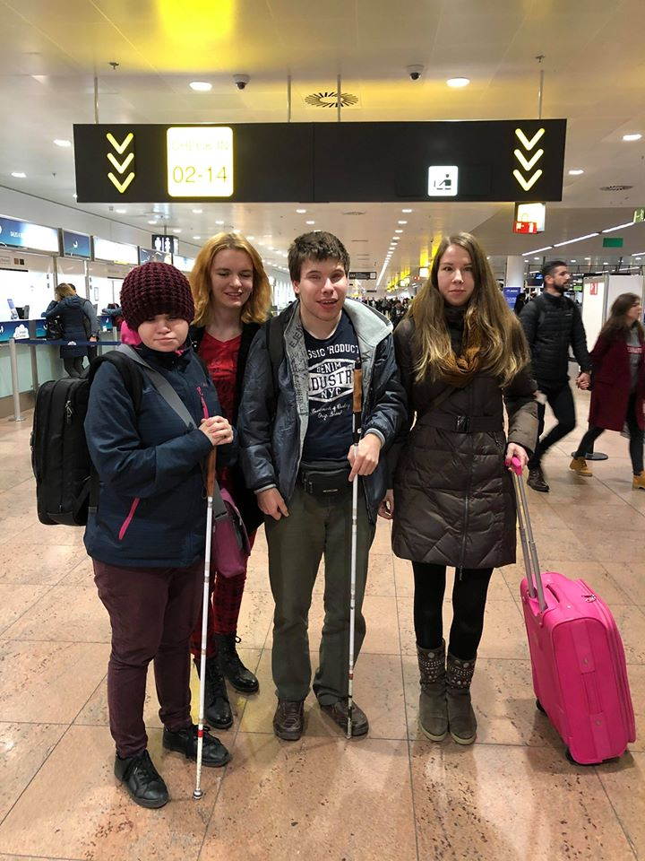 Four people -- three girls and one boy standing next to each other on an aiport