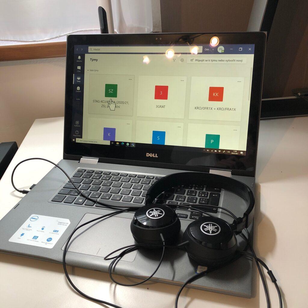 notebook, ve kterém je otevřený program ms teams, vedle něj leží sluchátka
